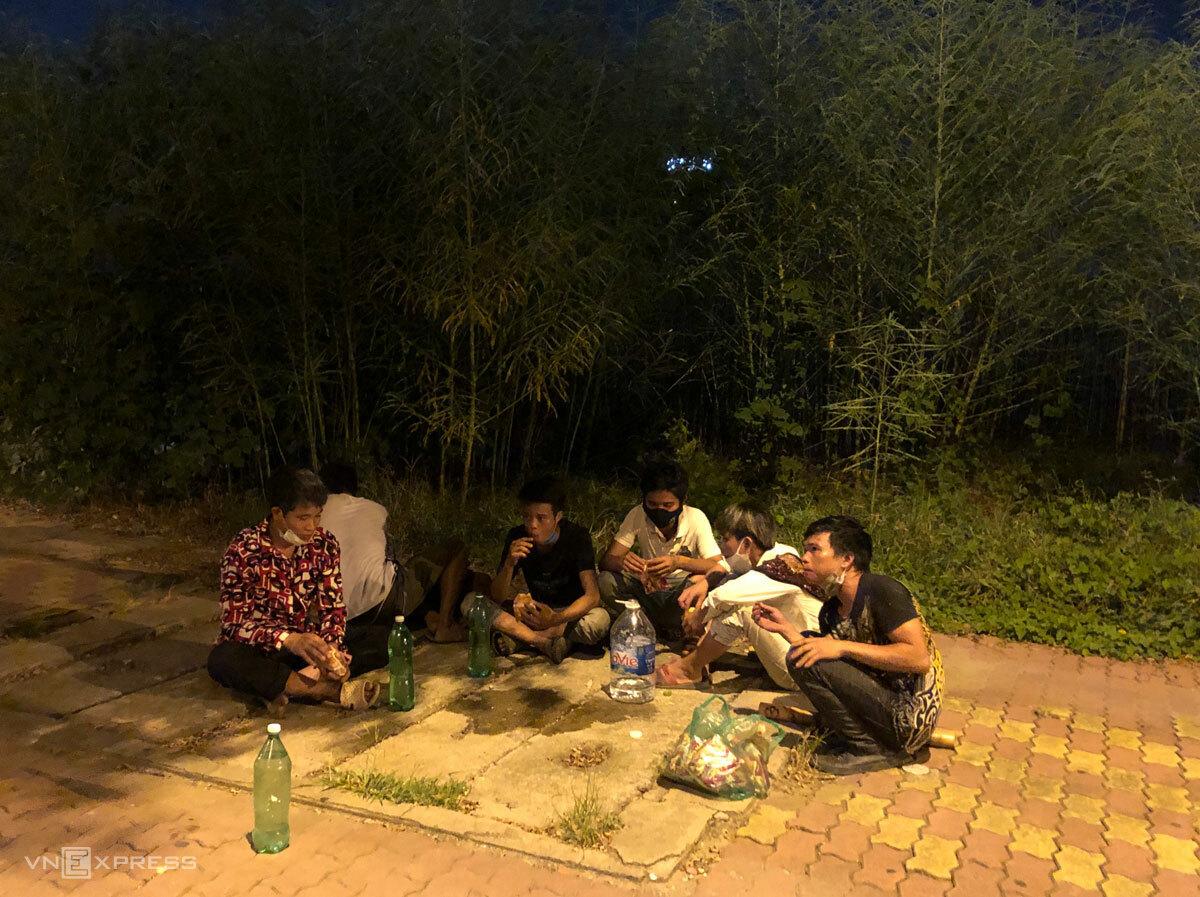 22h đêm 16/8, họ ngồi nghỉ bên vệ đường Phạm Hùng, ăn bánh uống nước để lấy sức đi bộ về quê. Ảnh: Hồng Chiêu