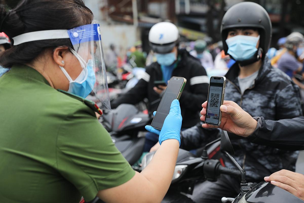 Công an kiểm tra mã QR Code của người dân đi đường ở TP HCM. Ảnh: Quỳnh Trần.
