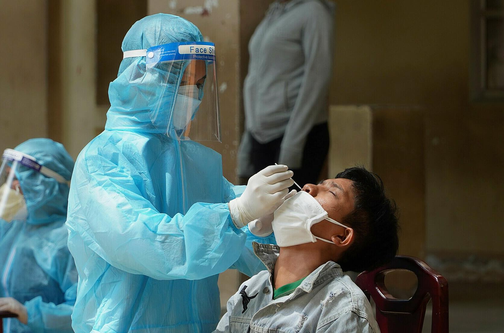 Nhân viên y tế lấy mẫu xét nghiệm người dân ở phường Hưng Long, TP Phan Thiết. Ảnh: Việt Quốc
