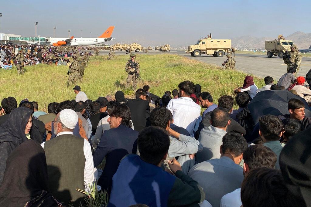 Binh sĩ và thiết giáp Mỹ đứng gác trước dòng người chờ di tản ở sân bay Kabul hôm 16/8. Ảnh: AP.