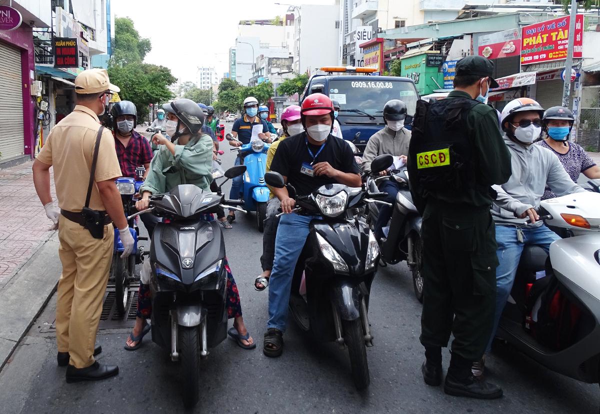 Cảnh sát kiểm tra giấy tờ người qua chốt đường Nơ Trang Long, quận Bình Thạnh, chiều 17/8. Ảnh: Hà An