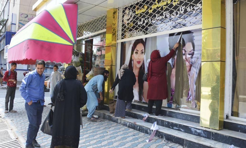 Nhân viên một tiệm thẩm kỹ ở Kabul bóc ảnh quảng cáo in hình phụ nữ hôm 15/8. Ảnh: Kyodo News