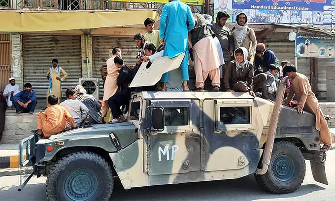 Các tay súng Taliban và dân địa phương ngồi trên một chiếc Humvee trên đường ở tỉnh Laghman, Afghanistan ngày 15/8. Ảnh: AFP.