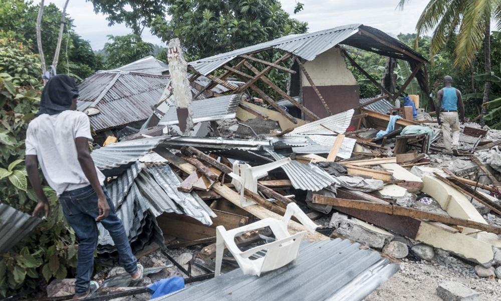 Người dân đứng cạnh một ngôi nhà bị phá hủy sau trận động đất gần Camp-Perrin, Haiti hôm 16/8. Ảnh: AFP.