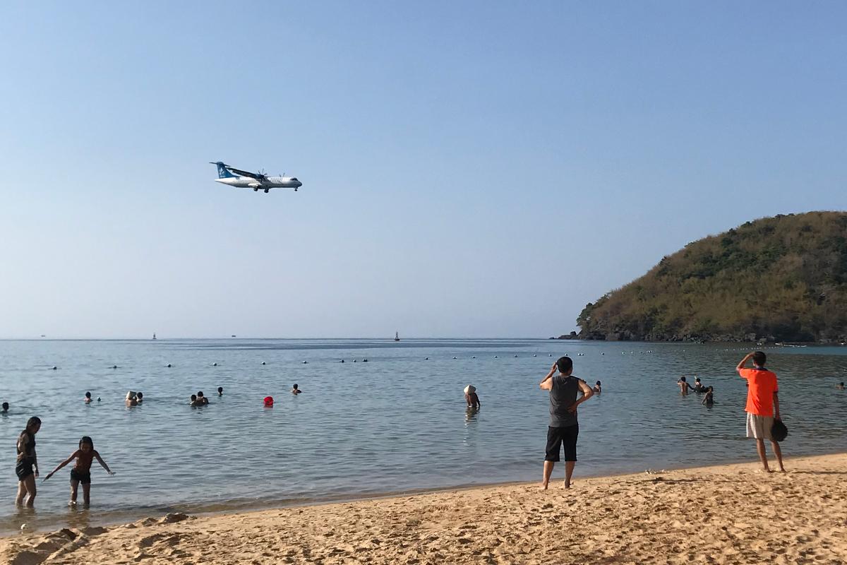 Khách du lịch ngắm máy bay hạ cánh gần bãi biển Đầm Trầu, Côn Đảo. Ảnh: Anh Duy.