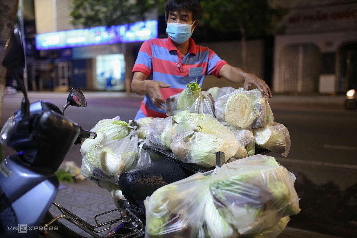 Ông Huỳnh Trí Đức xếp rau, củ, quả trong các túi nylon để đi phát cho dân, lúc 21h30 ngày 17/8. Ảnh: Nguyễn Đông.