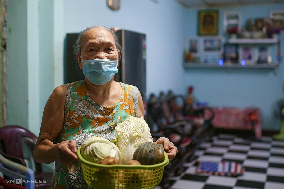 Cụ Lê Thị Chánh với phần rau, củ, quả vừa được nhận, tối 17/8. Ảnh: Nguyễn Đông.