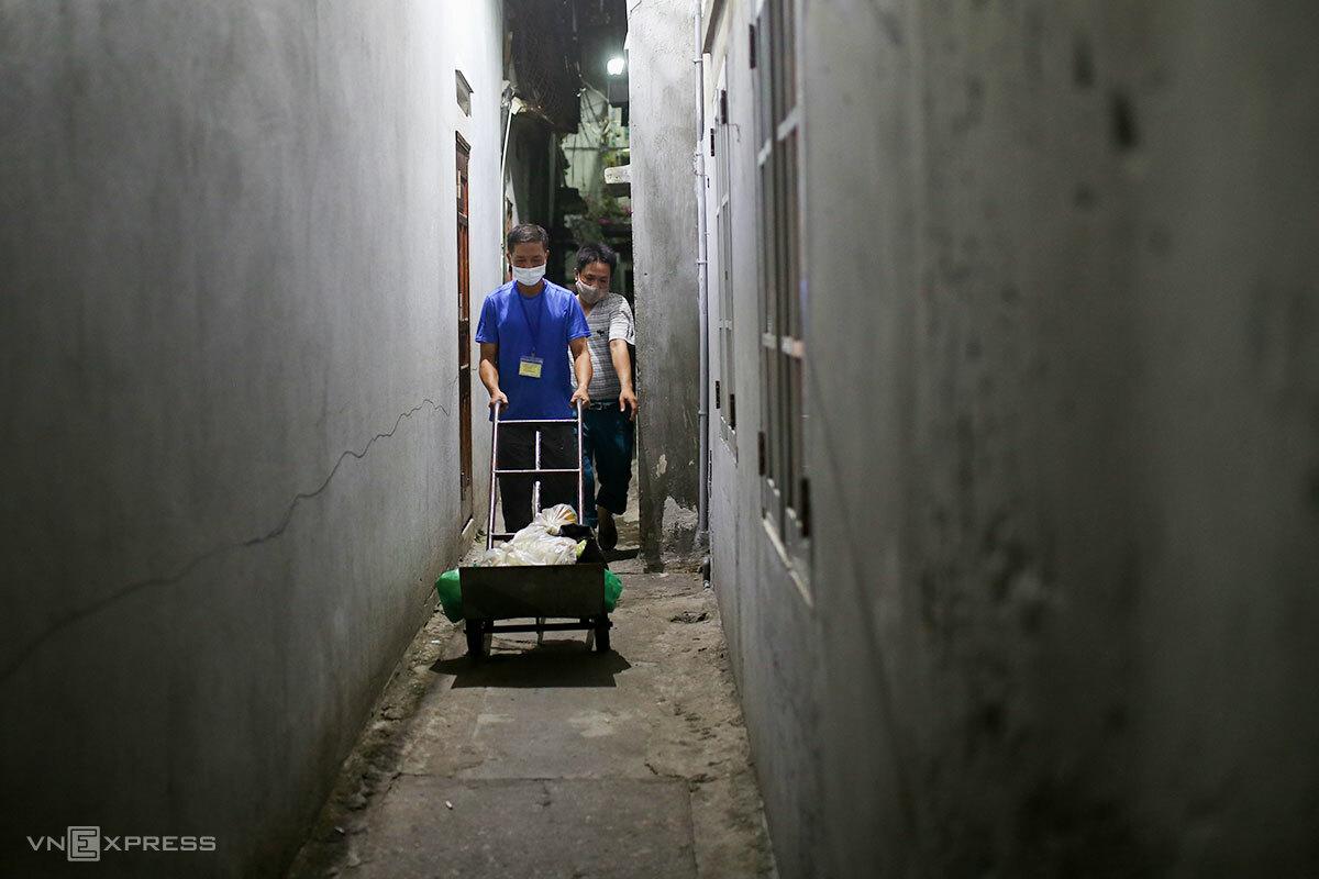 Các tình nguyện viên Ban điều hành dân cư tổ 18, phường Tân Chính, len lỏi vào các ngõ nhỏ để phân phát rau, củ cho bà con ngay trong đêm. Ảnh: Nguyễn Đông.