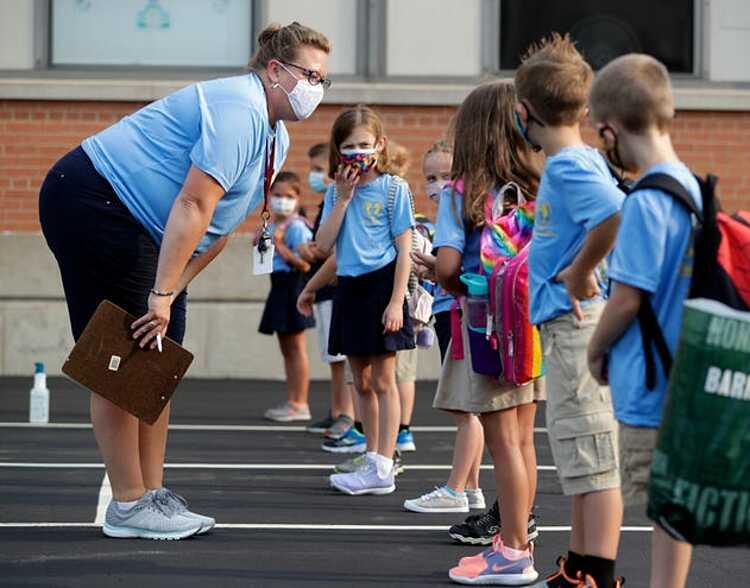 Giáo viên lớp 1 Jessica Johnson hỏi học sinh có em nào bị ốm hoặc ở gần người bị ốm không trước ngày đầu tiên khai giảng ở De Pere, bang Wisconsin, ngày 26/8/2020. Ảnh: AP