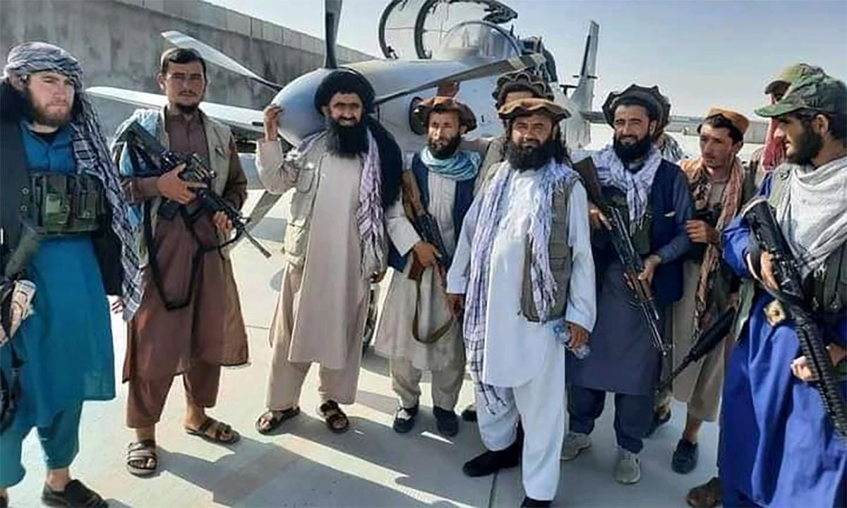 Các tay súng Taliban chụp ảnh trước cường kích A-29 không quân Afghanistan bỏ lại ở Mazar-i-Sharif. Ảnh: Twitter/worldonalert.