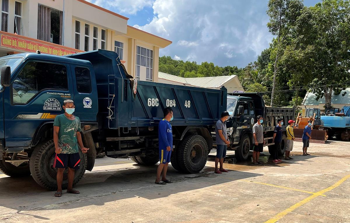 Nhóm người cùng phương tiện khai thác đất, cát trái phép bị đưa về cơ quan công an ở Phú Quốc. Ảnh: Dương Đông