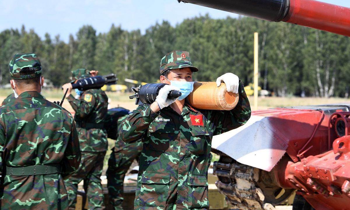 Thành viên đội Việt Nam đưa đạn và liều phóng về xe tăng hôm 18/8. Ảnh: QĐND.
