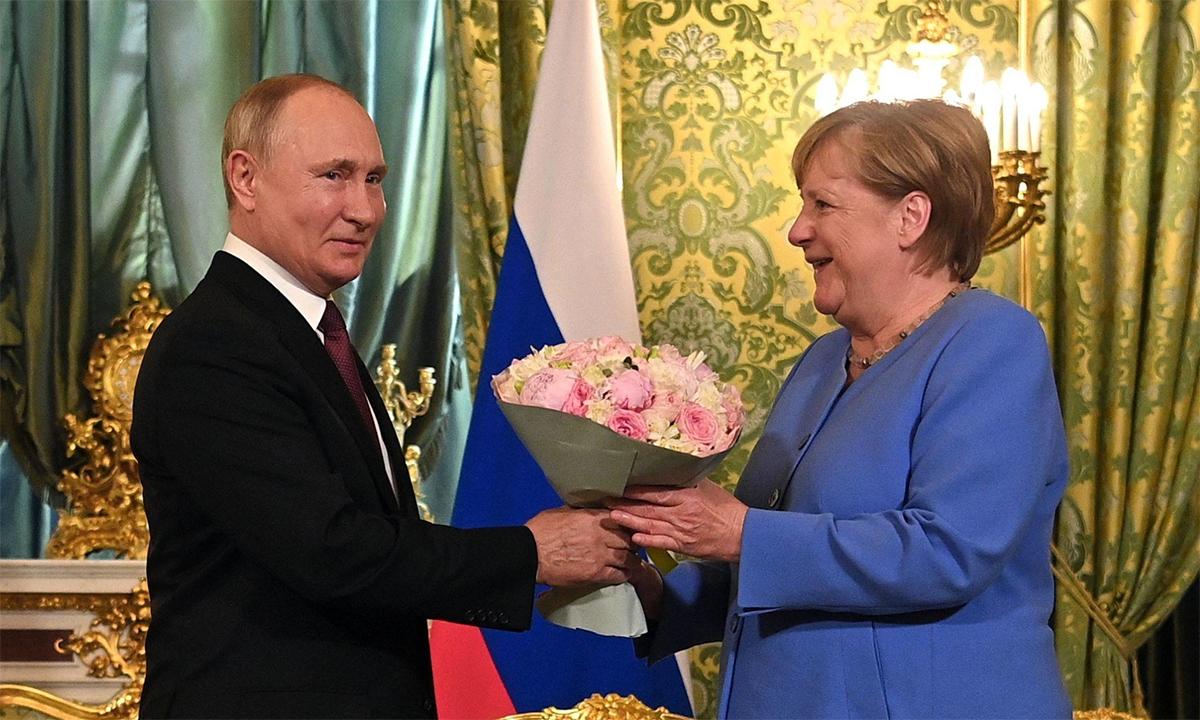 Tổng thống Nga Vladimir Putin (trái) tặng hoa cho Thủ tướng Đức Angela Merkel tại Moskva ngày 20/8. Ảnh: AFP.