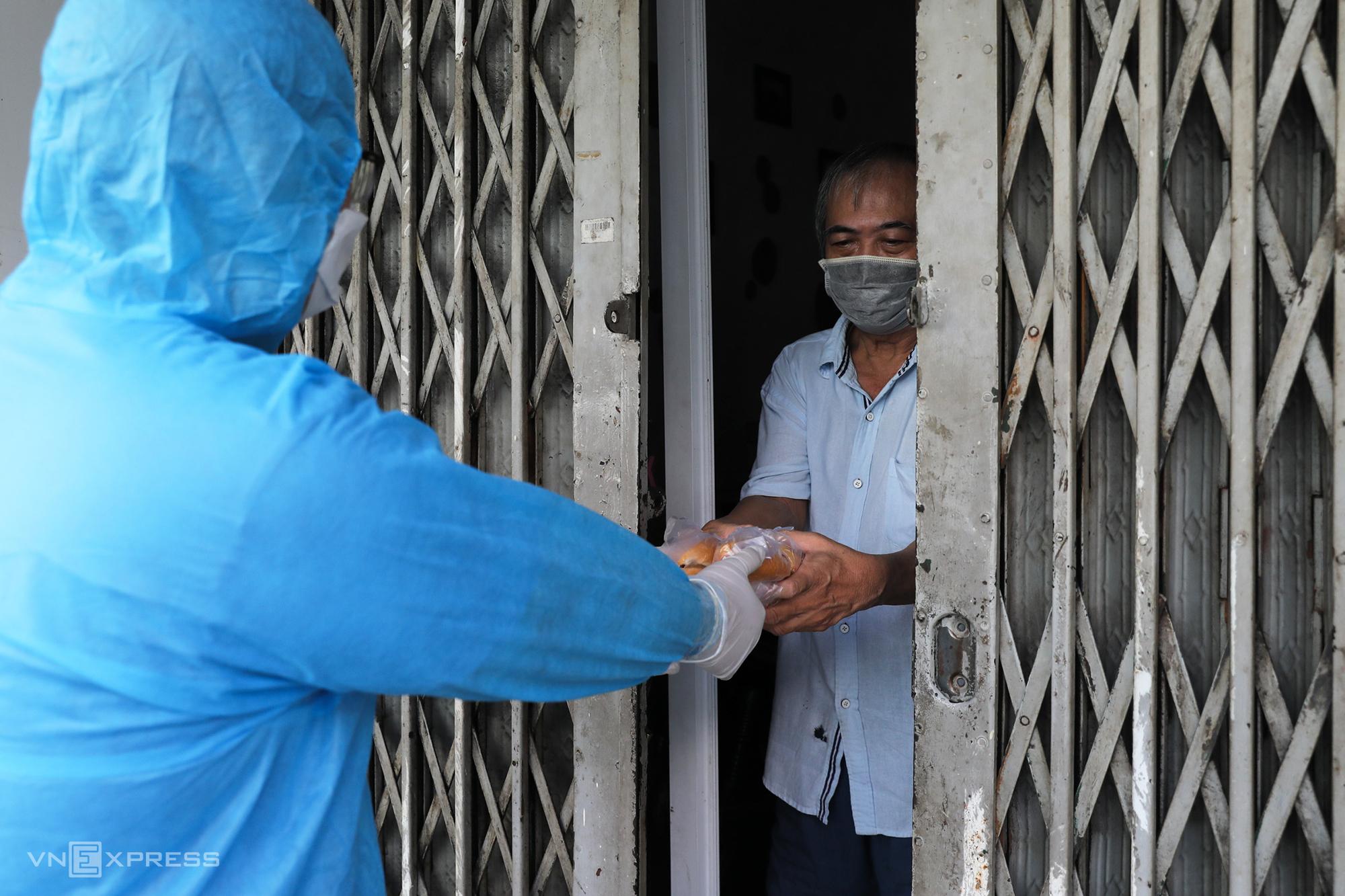 Tình nguyện viên tiếp tế nhu yếu phẩm cho từng nhà trong khu phong toả trên đường Vườn Chuối (quận 3), ngày 30/7. Ảnh: Quỳnh Trần