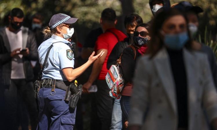 Nữ cảnh sát New South Wales nói chuyện với những người xếp hàng chờ tiêm vaccine Covid-19 tại Sydney hôm 16/8. Ảnh: AFP.