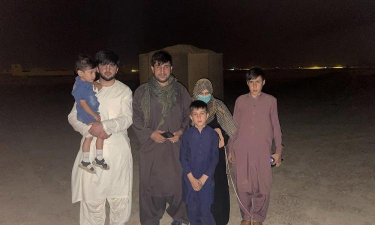 Mohammad Khalid Wardak (đeo khăn xanh) cùng gia đình tại một khu vực ở Afghanistan sau khi được quân đội Mỹ cùng đồng minh giải cứu hôm 18/8. Ảnh: AP.
