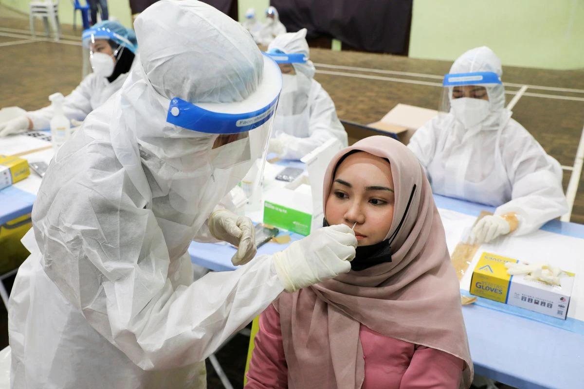 Một cô gái làm xét nghiệm nCoV ở Malaysia hồi tháng 5. Ảnh: Reuters.
