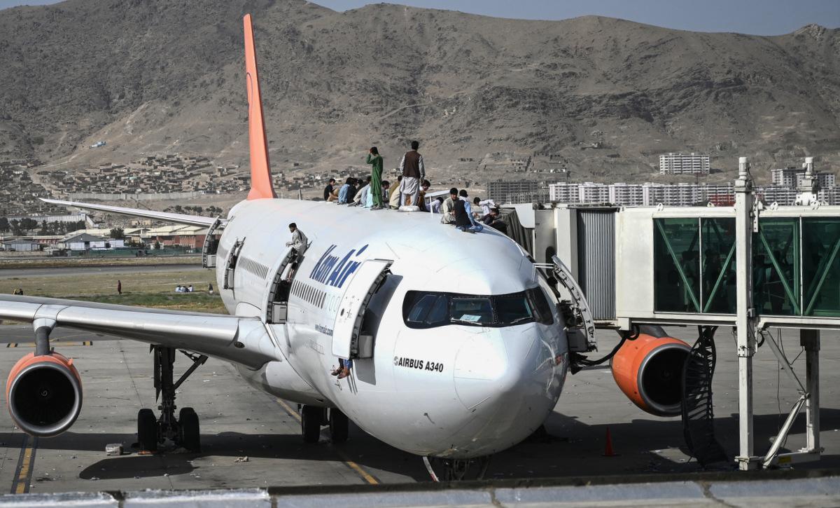 Người dân Afghanistan trèo lên máy bay của Kam Air tại sân bay Kabul hôm 16/8. Ảnh: AFP.