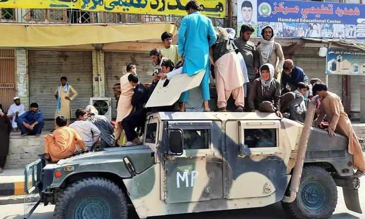 Các tay súng Taliban và dân địa phương ngồi trên một chiếc Humvee ở tỉnh Laghman, Afghanistan, hôm 15/8. Ảnh: AFP.