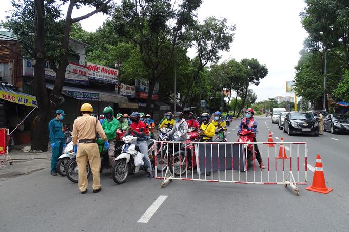 Nhiều shipper chờ kiểm tra giấy tờ qua chốt kiểm soát đường Đinh Bộ Lĩnh, quận Bình Thạnh, chiều 25/7. Ảnh: Hà An