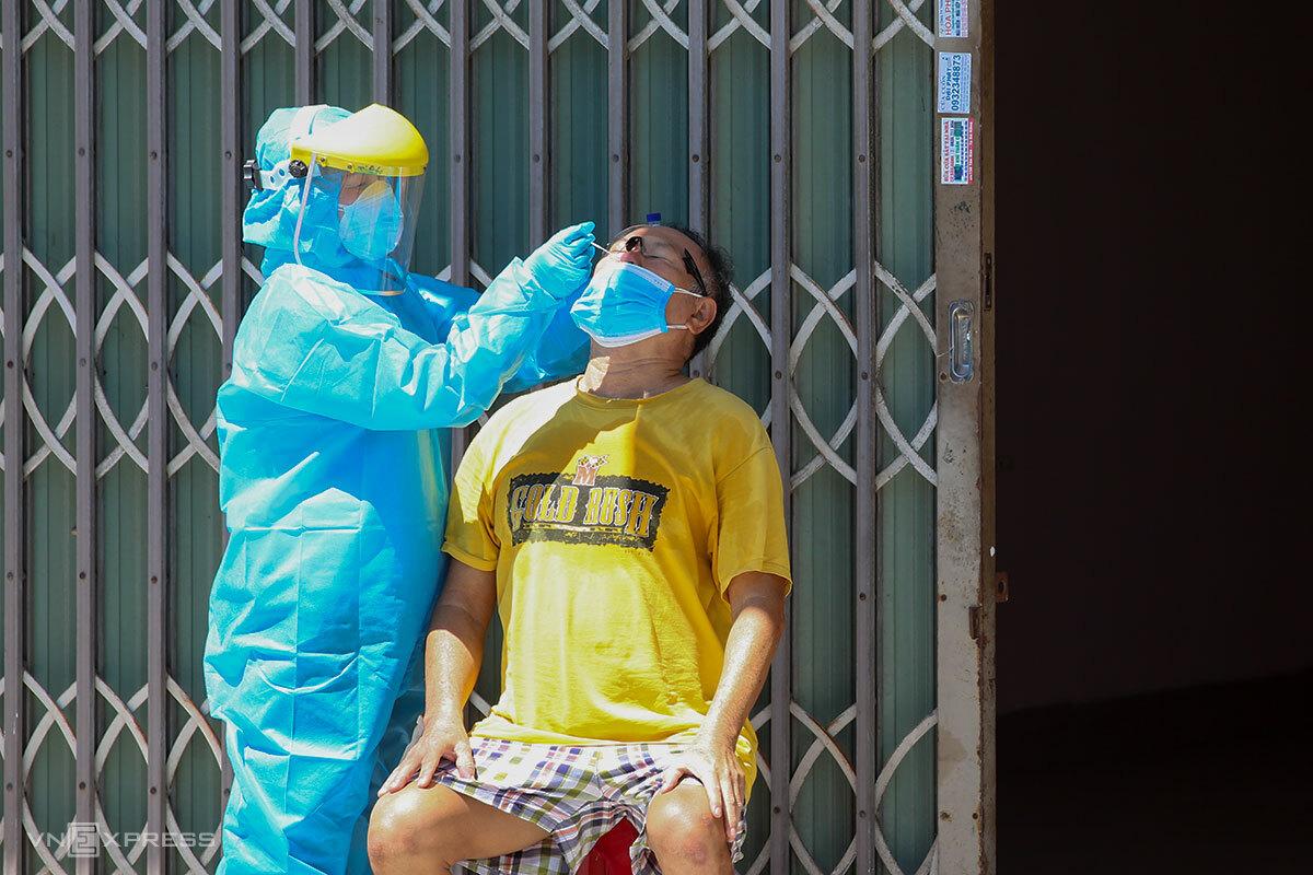 Nhân viên y tế lấy mẫu xét nghiệm lại cho 1 F0 đã khỏi bệnh, trên đường Ngô Quyền, quận Sơn Trà, ngày 17/8. Ảnh: Nguyễn Đông.
