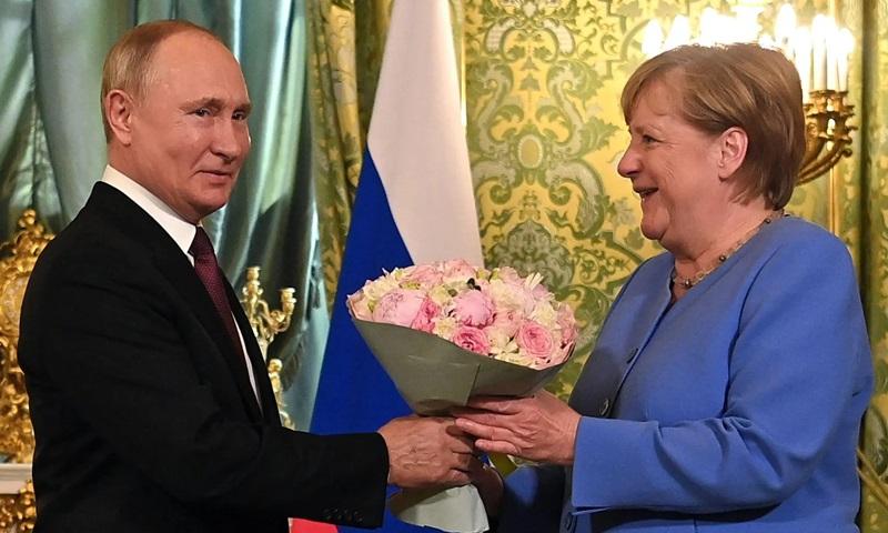 Putin tặng hoa cho Merkel trước khi hội nghị thượng đỉnh tại Điện Kremlin bắt đầu hôm 20/8. Ảnh: AFP.