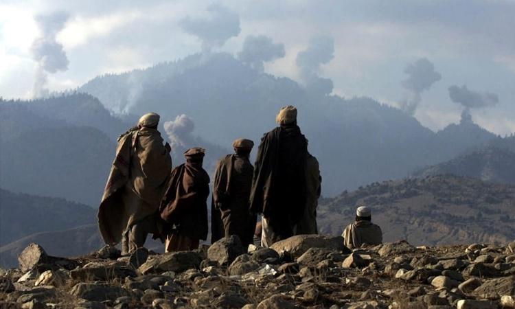 Các chiến binh chống Taliban ở Afghanistan đừng từ xa theo dõi các vụ đánh bom do Mỹ thực hiện ở vùng núi Tora Bora trong cuộc săn lùng al-Qaeda ngày 16/12/2001. Ảnh: Reuters.
