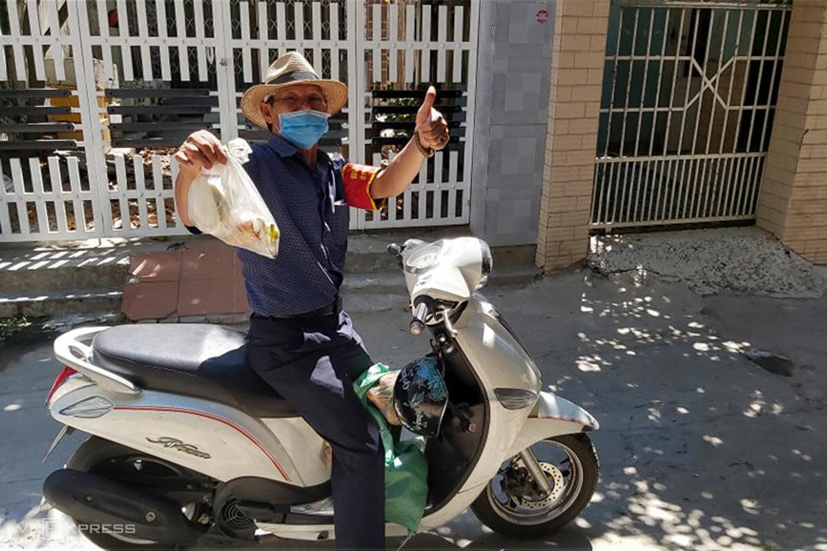 Ông Đinh Văn Tuấn trong lần phát rau, củ cho người dân trong hẻm đường Nguyễn Phước Nguyên, ngày 18/8. Ảnh: Quang Huy.