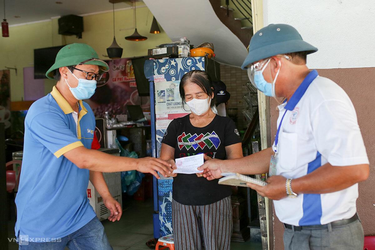 Anh Nguyễn Lương Ái (áo xanh) hướng dẫn người dân điền thông tin vào phiếu đăng ký xét nghiệm. Ảnh: Nguyễn Đông.