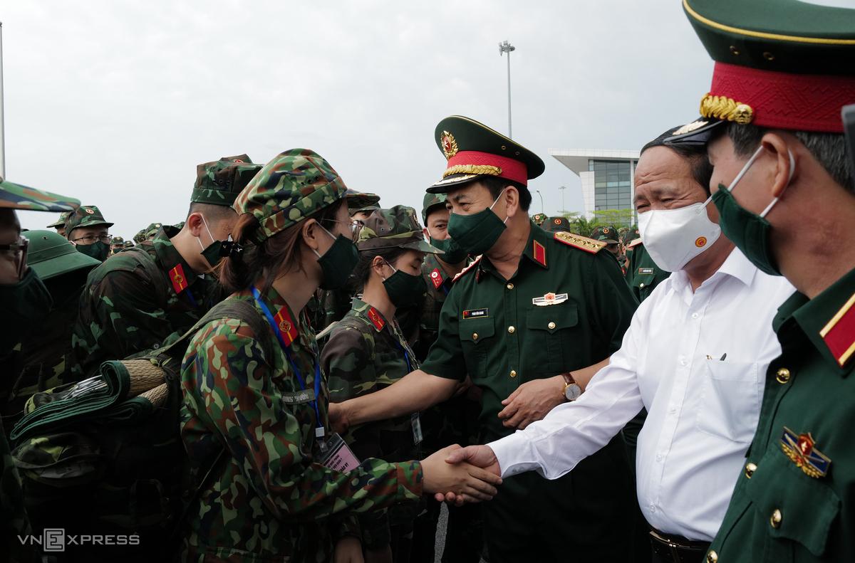 Phó thủ tướng Lê Văn Thành (áo trắng) và Đại tướng, Bộ trưởng Quốc phòng Phan Văn Giang động viên lực lượng quân y vào TP HCM chi viện chống dịch, tại sân bay Nội Bài, trưa 23/8. Ảnh: Ngọc Thành