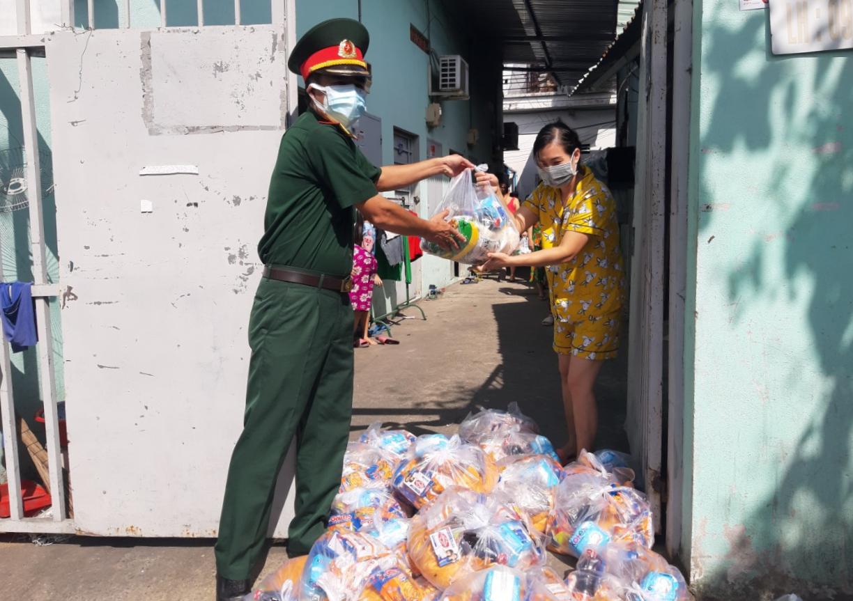 Quân đội trao quà cho dân tại một con hẻm ở quận 7, sáng 23/8. Ảnh: Hạ Giang