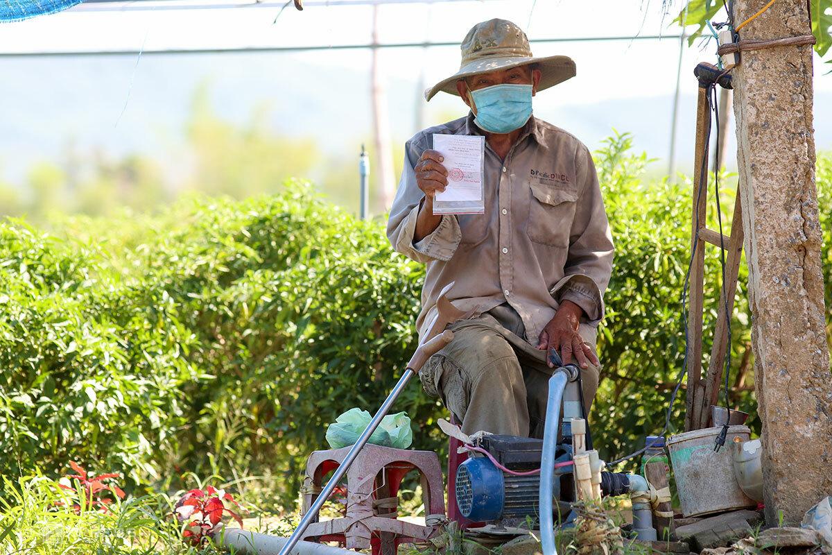 Ông Đấu giấy xác nhận được ra đường để đi làm đồng. Ảnh: Nguyễn Đông.