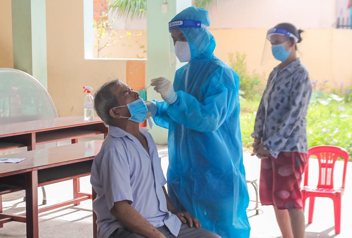 Nhân viên lấy mẫu xét nghiệm trong khu vực siết chặt, đông cứng để bóc tách F0 ra khỏi cộng đồng ngày 23/8. Ảnh: Thanh Liêm