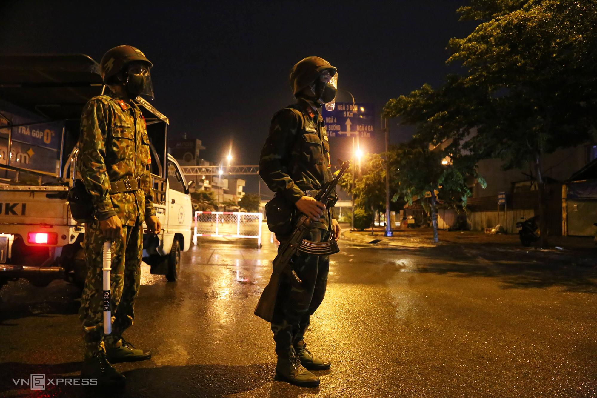 Hai chiến sĩ làm nhiệm vụ tại chốt kiểm soát cầu Trường Đai, quận 12, sau 0h ngày 23/8. Ảnh: Đình Văn