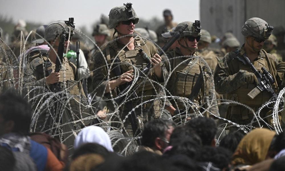Lính Mỹ đứng gác sau hàng rào thép gai, khi người Afghanistan ngồi bên vệ đường gần khu vực quân sự của sân bay ở Kabul hôm 20/8, với hy vọng rời khỏi đất nước sau khi Taliban tiếp quản. Ảnh: AFP.