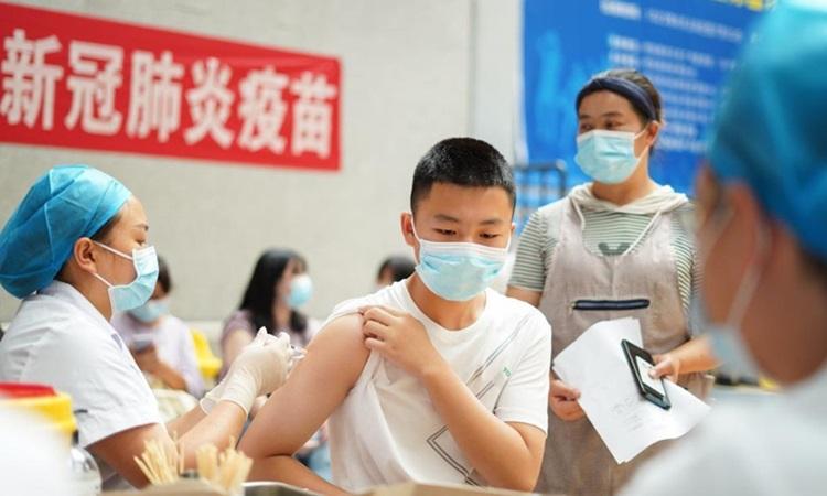 Nhân viên y tế tiêm vaccine Covid-19 cho học sinh ở tỉnh Quý Châu, tây nam Trung Quốc hôm 12/8. Ảnh: Xinhua.