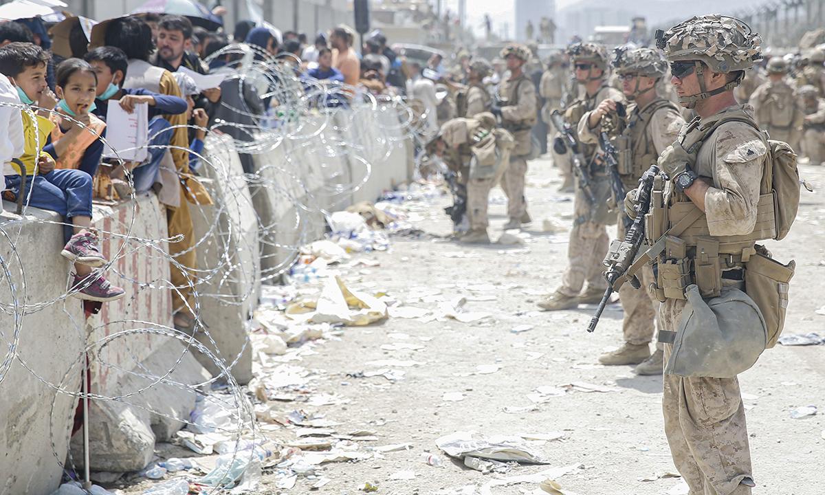 Các binh sĩ thủy quân lục chiến Mỹ (bên phải) đứng gác dọc theo hàng rào ngoài sân bay Hamid Karzai ở Kabul ngày 20/8. Ảnh: USMC.