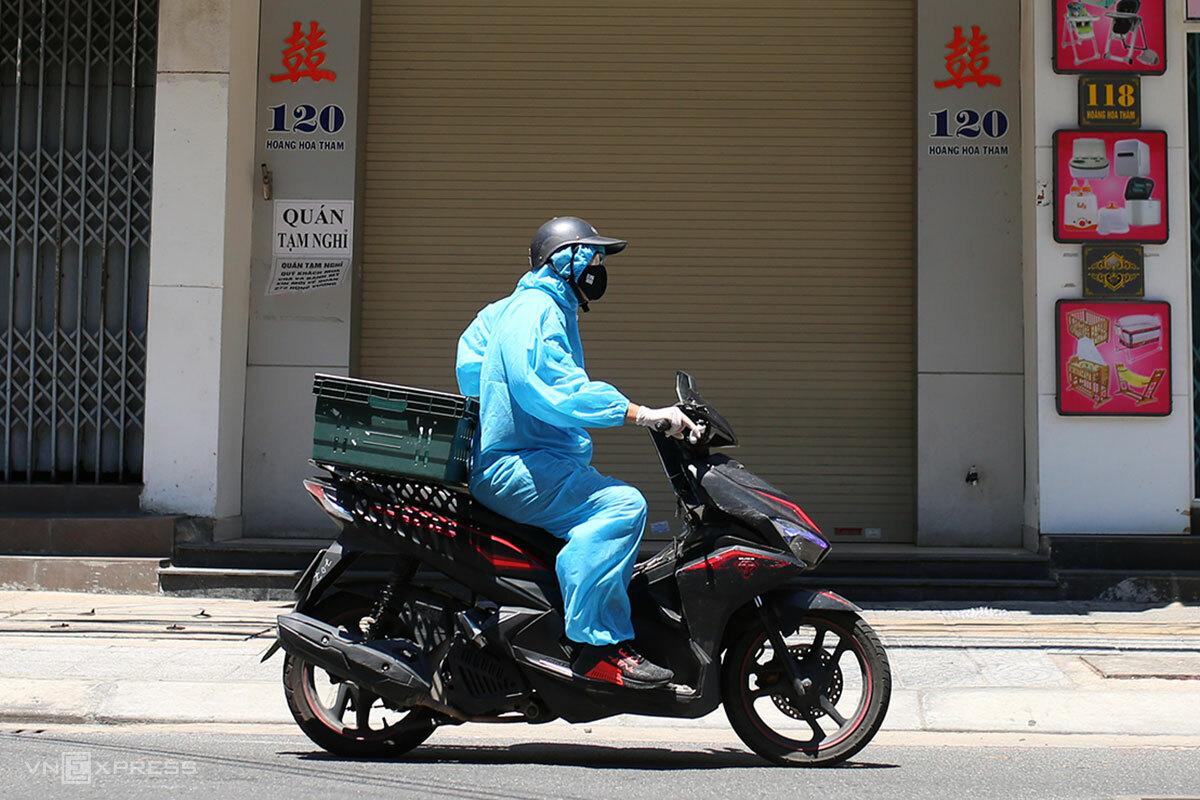 Shipper mang đồ bảo hộ đi giao hàng, trưa 24/8. Ảnh: Nguyễn Đông.