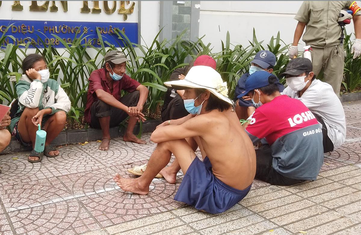 Người sống ở gầm cầu Móng, vỉa hè dọc đường Võ Văn Kiệt được quận 4 đưa về nơi tập trung. Ảnh: Đinh Sự