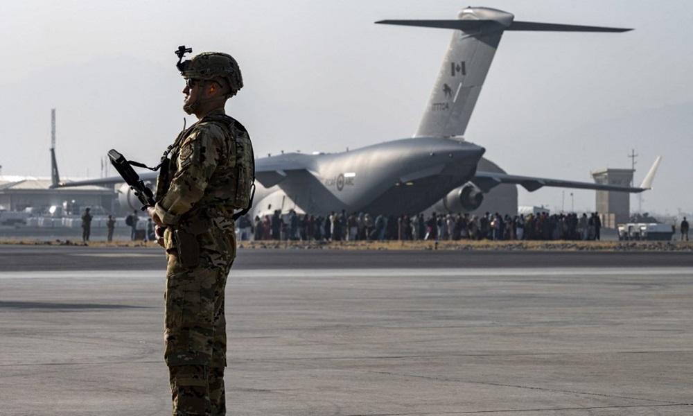 Lính Mỹ đứng gác tại sân bay Kabul, Afghanistan hôm 20/8, phía xa là đoàn người đang xếp hàng lên vận tải cơ quân sự C-17 của Không quân Mỹ. Ảnh: AFP.