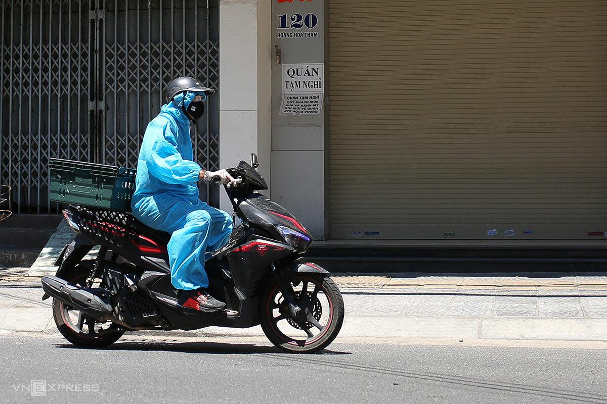 Shipper mặc đồ bảo hộ đi giao hàng, ngày 24/8. Ảnh: Nguyễn Đông.