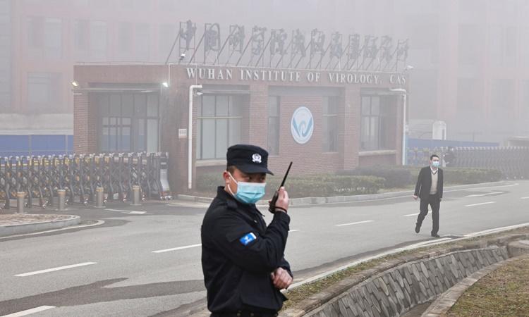 Nhân viên an ninh gác bên ngoài Viện Virus học Vũ Hán khi các chuyên gia WHO đến thăm cơ sở này ngày 3/2. Ảnh: Reuters.