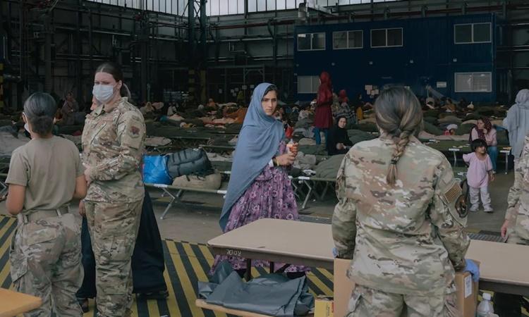 Một phụ nữ Afghanistan chờ nhận tã trong nhà chứa máy bay được chuyển đổi thành nơi lưu trú thuộc căn cứ không quân Ramstein, Đức, ngày 24/8. Ảnh: Washington Post.