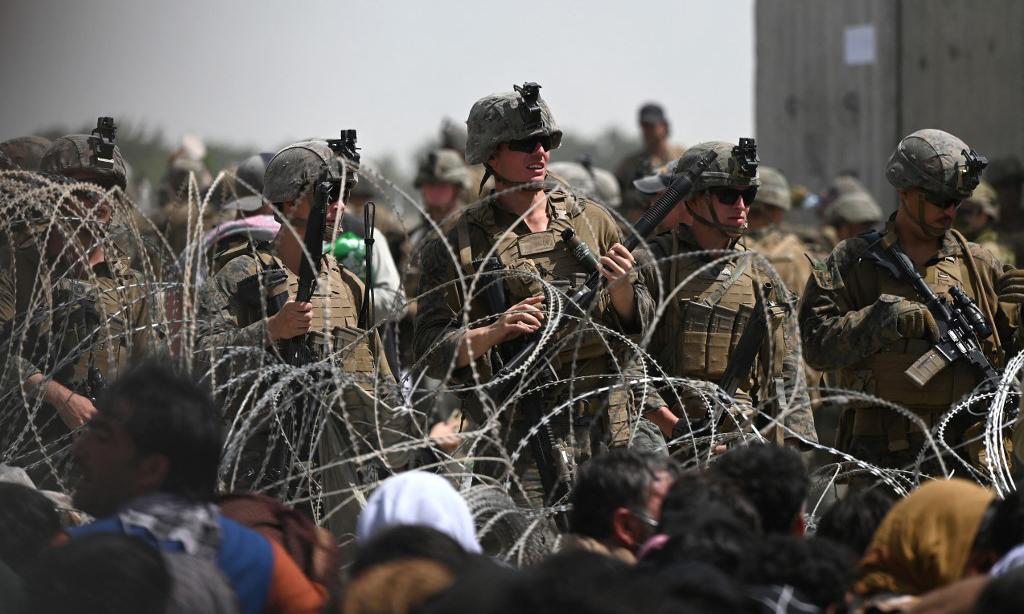 Lính Mỹ đứng sau hàng rào dây thép gai khi những người Afghanistan tập trung gần sân bay Kabul hôm 20/8. Ảnh: AFP.