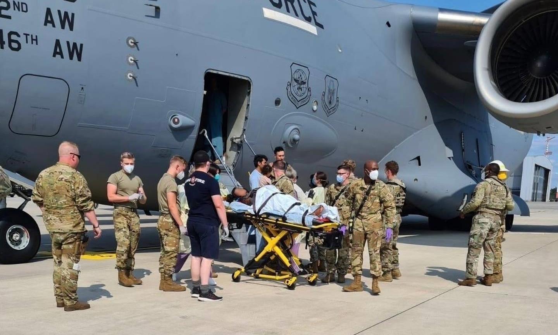 Nhân viên y tế hỗ trợ gia đình Afghanistan rời khỏi máy bay C-17 Reach 828 của Không quân Mỹ sau khi người mẹ hạ sinh bé gái tại căn cứ không quân Ramstein ở Đức hôm 21/8. Ảnh: Không quân Mỹ