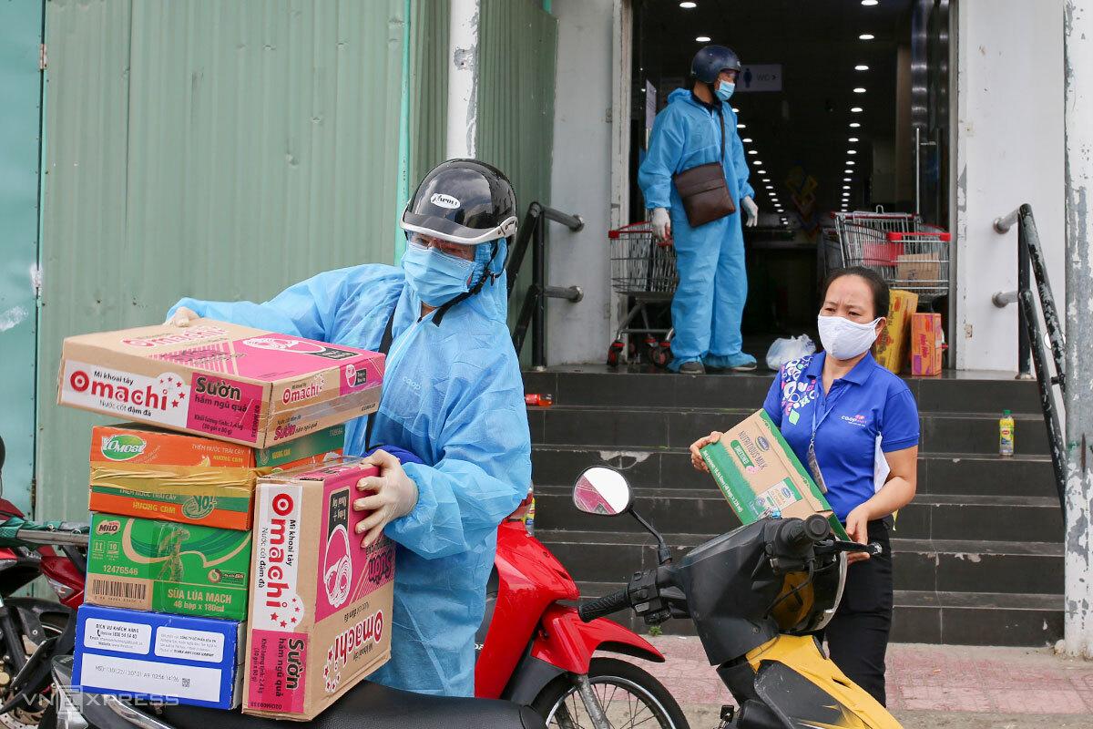 Các shipper của siêu thị, cửa hàng tiện lợi đang hoạt động hết công suất để vận chuyển hàng hóa đến các khu dân cư, ảnh chụp sáng 26/8. Ảnh: Nguyễn Đông