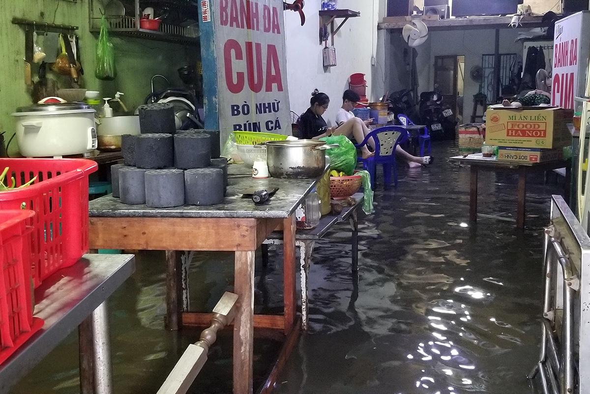 Mưa lớn đã khiến hàng nghìn ngôi nhà mặt phố, trong ngõ bị ngập nước, sinh hoạt bị đảo lộn. Trong ảnh, một ngôi nhà mặt đường Nguyễn BỈnh Khiêm kinh doanh bán bánh đa cua mang về ngập nước. Ảnh: Giang Chinh