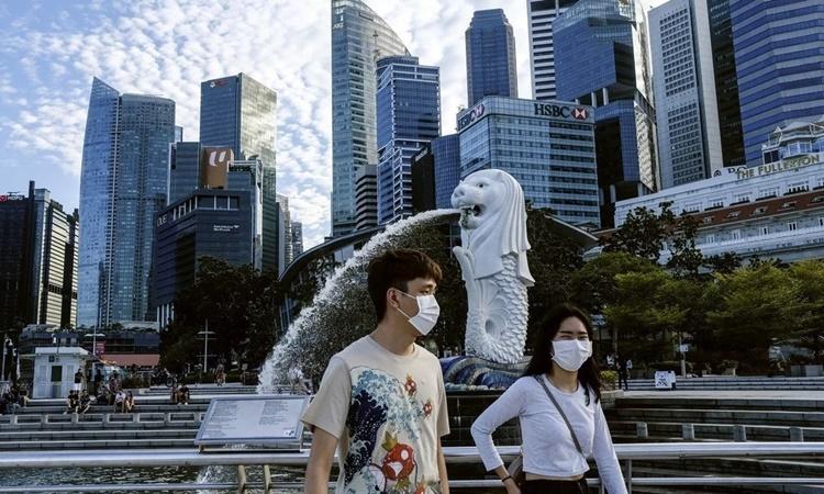 Hai bạn trẻ đeo khẩu trang đi qua bức tượng sư tử mình cá Merlion nổi tiếng của Singapore. Ảnh: AP.