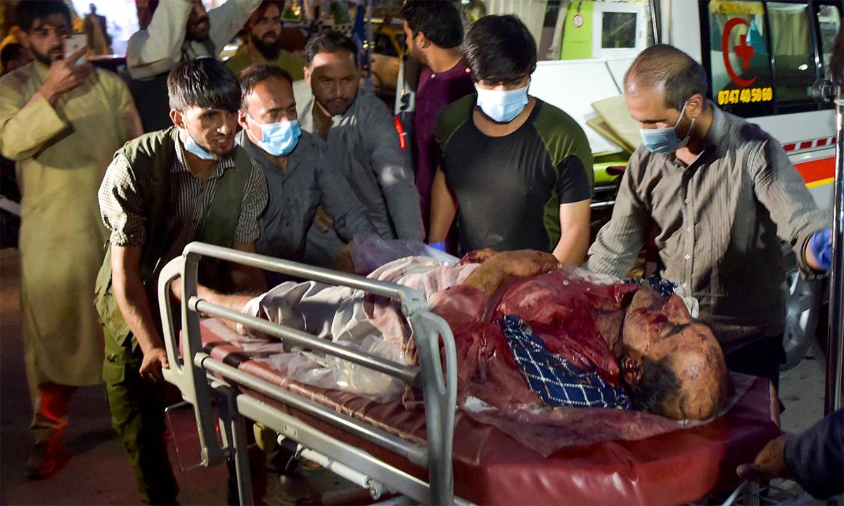 Tình nguyện viên và nhân viên y tế Afghanistan đưa một người đàn ông bị thương trong vụ đánh bom ở sân bay Kabul đi điều trị ngày 26/8. Ảnh: AFP.