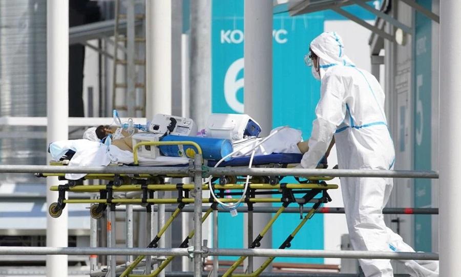 Nhân viên y tế mặc đồ bảo hộ di chuyển một bệnh nhân Covid-19 tại bệnh viện ở ngoại ô Moskva, Nga tháng trước. Ảnh: Reuters.